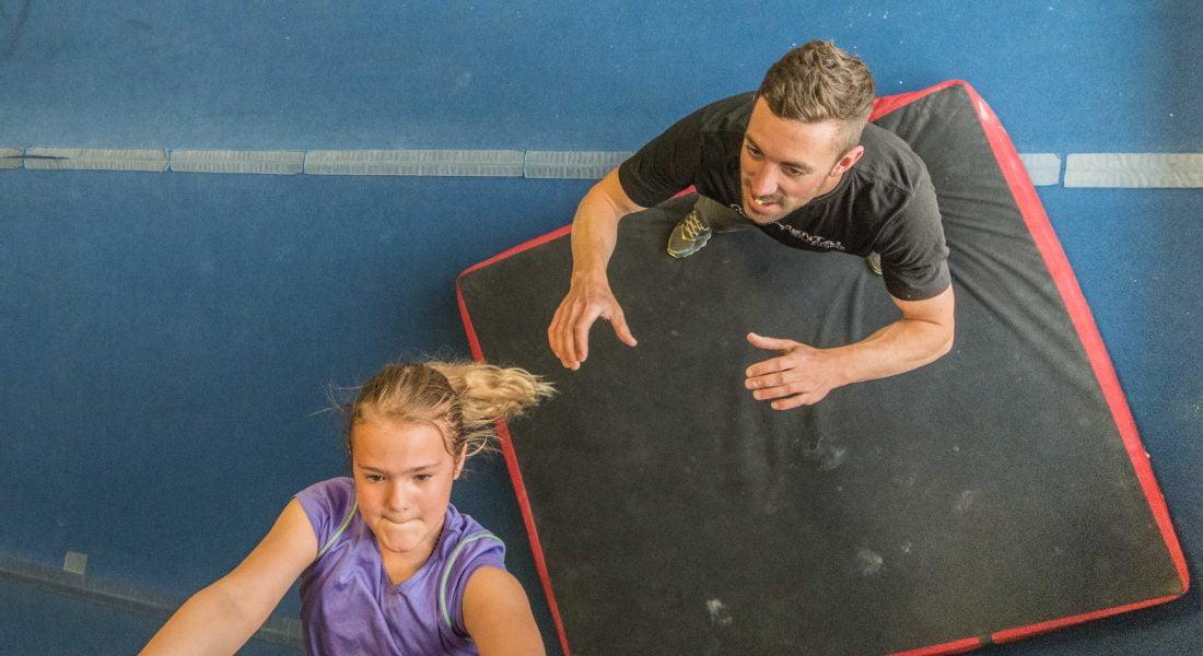 Charlie Manganiello spots a child as she climbs in the climbing gym