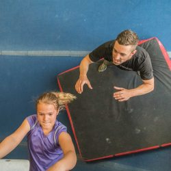 Charlie Manganiello spots a child as she climbs in the climbing gym